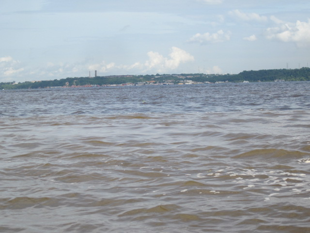 At the point of the Meeting of the Waters, with the muddy Solimoes River closer in the picture and Rio Negro in the back