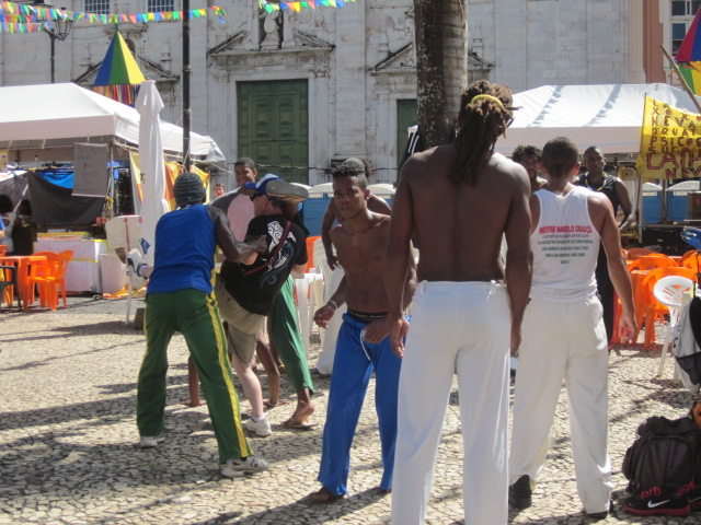 Some locals trying to teach a tourist the art of capoeira, a local style of martial arts